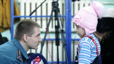 An Emergency Situations employee speaks to a girl in an evacuation centre near a collapsed section of the apartment building in Magnitogorsk.