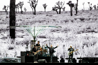The band play in front of Anton Corbijn's footage of Joshua Tree National Park.