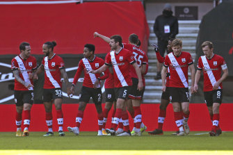 Southampton players celebrate the own goal that put them ahead against Arsenal.