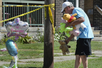 Paul Laughlin, 57, places stuffed animals outside a home where multiple people died in an early-morning fire.