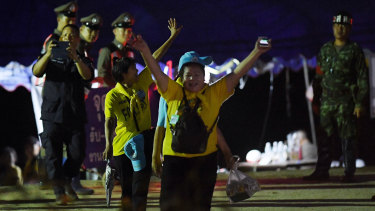 Thai volunteers cheer on news the boys and their coach had been rescued.