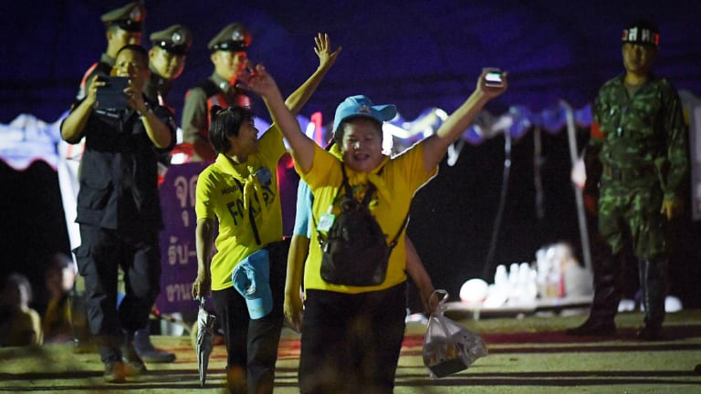 Thai volunteers cheering as they return from Tham Luang cave after all 13 have been rescued.