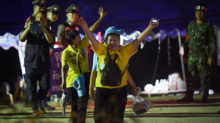 Thai volunteers cheer as they return from Tham Luang cave.