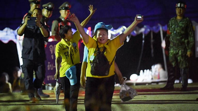 Thai volunteers cheer as they return from Tham Luang cave after the group was rescued.