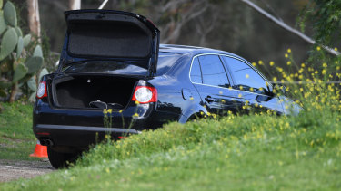 Another car, believed to have been driven by the suspect, down the road from the rammed police car.