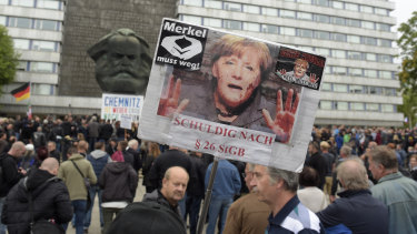 A protester holds a poster with a photo of Angela Merkel reading 'Merkel must go'  in Chemnitz, eastern Germany, on Saturday.