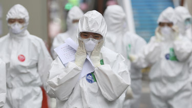 A medical staff member adjusts her face mask as she arrives for a duty shift at Dongsan Medical Center in Daegu, South Korea.