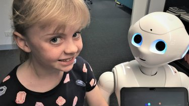 Ella, 7, and Pepper the Robot, at the Australian Centre for Robotic Vision.