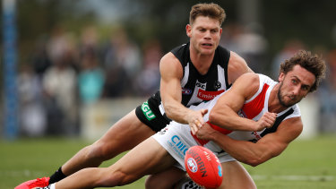 High intensity: St Kilda's Luke Dunstan gets a handpass away under pressure from Collingwood's Taylor Adams.