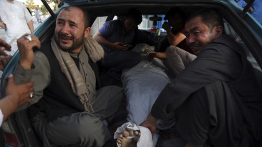 The body of a man is taken away for burial after the bombing in western Kabul.
