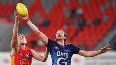 Tap and go: Gold Coast's Zac Smith (left) takes on Darcy Fort of the Cats.