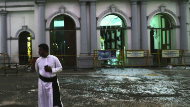 A Sri Lankan catholic priest stands near broken glass in front St. Anthony's Church in Colombo.