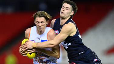 Lachie Whitfield is tackled by Josh Honey.