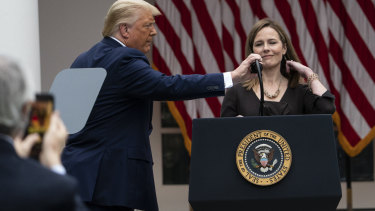 President Donald Trump adjusts the microphone as he announces Judge Amy Coney Barrett as his nominee to the Supreme Court.