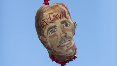 """Demonstrators carry a image representing the head of Governor Ricardo Rossello on a pike, with an inscription on its forehead that reads in Spanish """"Resign"""" during a march demanding the resignation of Governor Rossello, in San Juan."""
