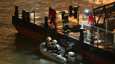 Responders sit in a rubber dinghy preparing for the search for victims.