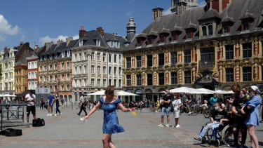 A woman dances by a cafe terrace in Lille, northern France.