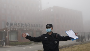 A security person moves journalists away from the Wuhan Institute of Virology after a World Health Organisation team arrived for a field visit in Wuhan in China's Hubei province.
