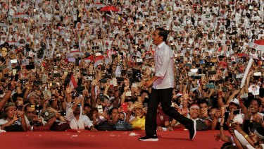 Indonesian President Jokowi runs to the stage at his final election rally in Jakarta on Saturday.
