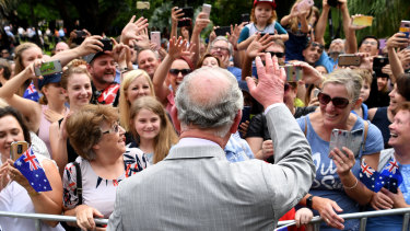 Prince Charles waves to cheering members of the public during a public walk through the Brisbane City Botanic Gardens.