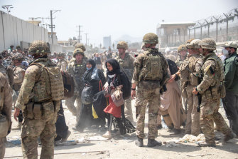 In an image provided by the Ministry of Defence, the British armed forces work with the US military to evacuate eligible civilians and their families from Kabul.