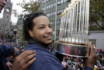 Manny Ramirez shows off Boston's World Series trophy after their drought-breaking 2004 win.