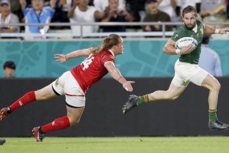 South Africa's Cobus Reinach runs clear of Canada's Jeff Hassler during the Rugby World Cup Pool B game at Kobe Misaki Stadium.