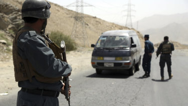 Afghan police officers search a vehicle at a checkpoint on the Ghazni highway.