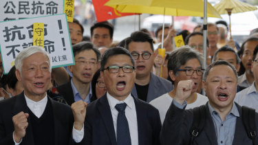 Occupy Central leaders, from right, Benny Tai, Chan Kin Man and Chu Yiu Ming shout slogans before entering a court in Hong Kong on Tuesday.