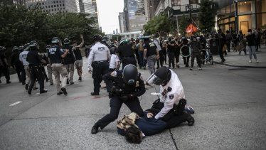 Police arresting protesters refusing to get off the streets during an imposed curfew in New York.