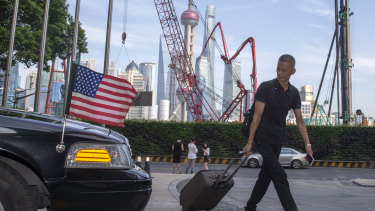 A traveller pulls a trolley past a US embassy car outside a hotel in Shanghai.