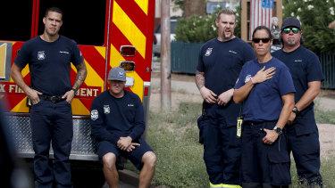 Firemen watch a motorcade carrying the casket of Senator John McCain.