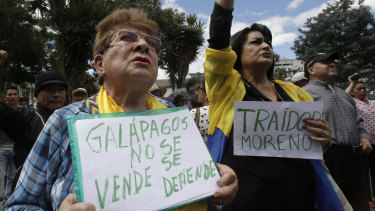 """A woman holds a sign with a message that reads in Spanish; """"Galapagos is not to be sold, but to be defended,"""" during a protest in Quito."""