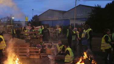Demonstrators stand in front of a makeshift barricade set up by the so-called yellow jackets to block the entrance of a fuel depot in Le Mans, France.