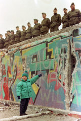A  young West German girl points to a large hole in the Berlin Wall on November 11, 1989.