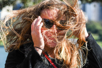 A tourist is caught in winds in the Botanic Gardens on Friday.