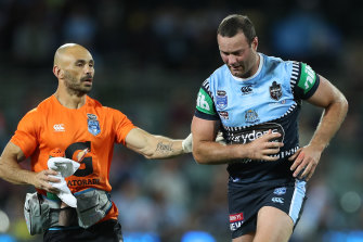 Boyd Cordner is assisted off Adelaide Oval for a head injury assessment by Roosters and Blues trainer Travis Touma.