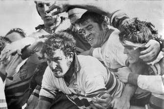 "Barry ""Tizza"" Taylor, second from right, protects Ken Taylor (no relation) in a rugby union match in 1972."