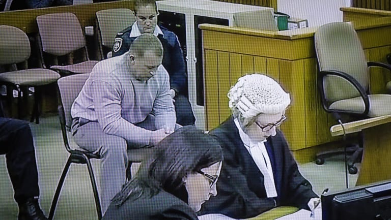 Graham Dillon listens to Justice John Burns as he is handed a sentence of 41 years and one month. Photo was taken from a television screen broadcasting the sentencing live for media within the Supreme Court.