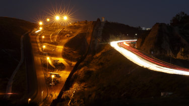 Floodlights from the US illuminate a border wall as traffic flows along a highway in Tijuana, Mexico.