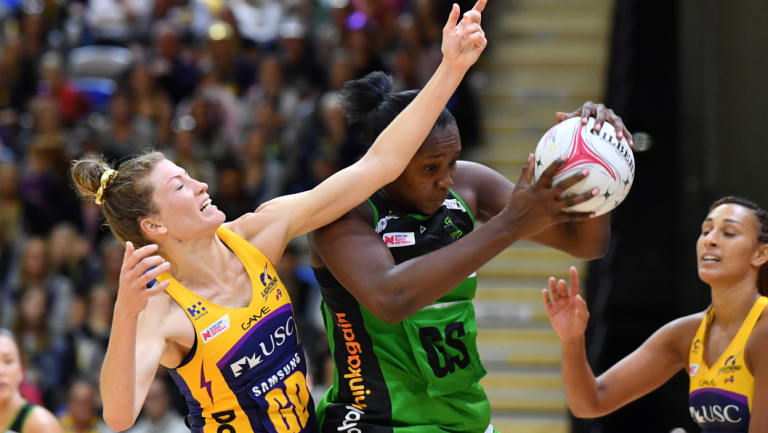 Fever's Jhaniele Fowler (centre) grabs the ball as Karla Pretorius of the Lightning (left) defends earlier in the season.
