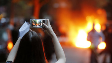 A young woman takes a picture of a burning barricade during a protest against the G20 in Hamburg,  Germany, in July.
