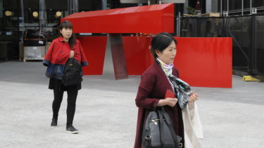 Yanjie Yang (left) and Xiaoyu Zhu leave the ACT Magistrates Court.