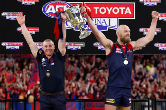 Melbourne coach Simon Goodwin and captain Max Gawn stand euphorically with premiership cup in-hand.