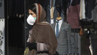 A woman walks as she wears a mask in  Tehran, Iran.