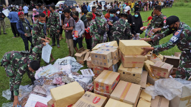 Indonesian soldiers distribute aid for those affected by the earthquake at a stadium in Mamuju on Sunday.