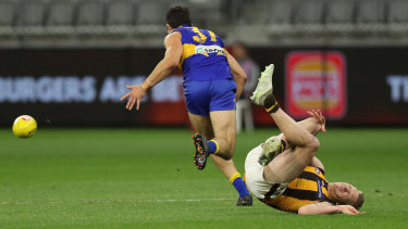 The Hawks defender clutches his knee after going down in a contest against West Coast's Tom Barrass.