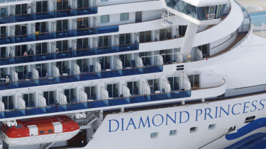 Some passengers are seen on the Diamond Princess as the cruise ship is anchored at Yokohama Port to replenish  supplies.
