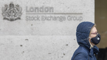 A pedestrian wears a protective face mask as she walks past the London Stock Exchange.
