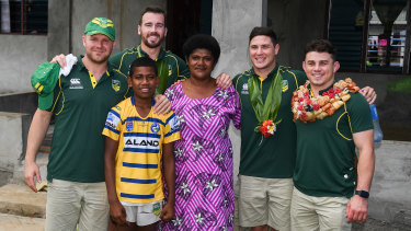 Parramatta Eels players pose with Maika Sivo's mother Mere and little brother Isaia, 12, in their teammate's hometown in Fiji.